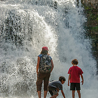 A mother and her children admire  Ouzel Falls near Big Sky, Montana.