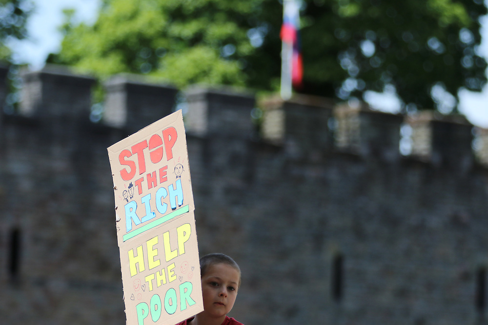A young boy takes part in an anti-austerity protest opposite Cardiff Castle