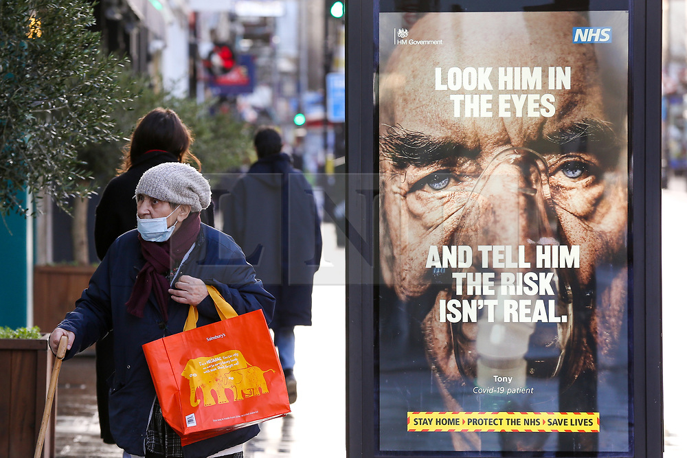 © Licensed to London News Pictures. 02/02/2021. London, UK. An elderly woman wearing a protective face covering walks past the government's 'Look him in the eyes - And tell him the risk isn't real.' awareness publicity campaign poster in Haringey, north London. Door-to-door testing for the South Africa coronavirus variant will begin certain postcodes in the London boroughs of Merton, Haringey and Ealing to avoid the spread of the virus. Minister are telling members of the public in areas where South Africa variant has been found to 'think again' before leaving home. Photo credit: Dinendra Haria/LNP