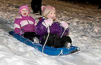 Autumn Hopler and Catja Kolanda are all smiles during their turn down the hill during the sledding party held at Laconia's new sledding hill Friday evening.  (Karen Bobotas/for the Laconia Daily Sun)