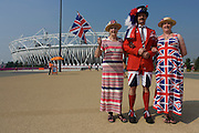A tall son in the middle accompanies his mother (l) and sister (R) in the Olympic Park during the London 2012 Olympics. Wearing Union Jack designs dresses and shorts plus a tie and flag to wave, the trio stand in front of the main Olympic stadium before the large crowds arrive later in the day. They have tickets to watch the Hockey and stand smiling as eccentric Brits wearing their national colours.