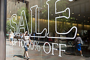 Retail store with white letters on the window glass Sale Up to 50% Off in Knightsbridge, London, United Kingdom.  People can be seen in the glass reflection.  Knightsbridge is an affluent area of London and famous for its high-end retail shops.
