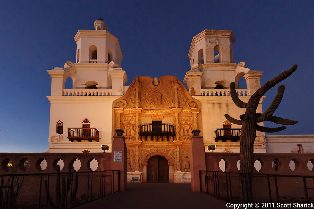 The sun has fallen as the clear night sky darkens behind the mission. Also known as the White Dove of the Desert.