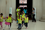 Interior view of the Great Court in The British Museum, London. Young school visitors arive in high visibility jackets.