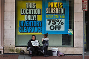 Homeless familly begging outside store with price reductions on Canal street on 11th March 2020 in New Orleans, Louisiana, United States. On the streets of the New Orleans, groups of homeless people perch outside of storefronts for hours. Loitering laws have been repeatedly ruled unconstitutional, and a persons mere presence in a public space is not illegal.
