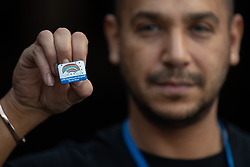 "© Licensed to London News Pictures . 22/04/2020. Manchester, UK. In an echo of Health Secretary Matt Hancock's pose with a ""CARE"" badge , Porter DANIEL TODD (35) , holds a commemorative badge , being given as a gift to those who have worked at the NHS Nightingale Hospital in Manchester . The National Health Service has built a 648 bed field hospital for the treatment of Covid-19 patients , at the historical railway station terminus which now forms the main hall of the Manchester Central Convention Centre . The facility is treating patients from across the North West of England , providing them with general medical care and oxygen therapy after discharge from Intensive Care Units . Photo credit : Joel Goodman/LNP"