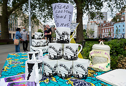 """© Licensed to London News Pictures; 07/06/2021; Bristol, UK. Mugs with the slogan """"Glad Colston's Gone!"""" are seen as people gather, place placards and chalk words at the Colston statue plinth in the city centre for the anniversary of when the statue of slave trader Edward Colston was toppled off the plinth and thrown into Bristol  docks one year ago today. Protesters toppled the statue on 07 June 2020 during a Black Lives Matter demonstration following the murder in the US of George Floyd a black man by a white police officer. The statue itself is being shown as it looked when it was retrieved from Bristol harbour at a temporary display in M Shed Museum with a survey by the We Are Bristol History Commission asking the city's citizens for their views on its long-term future. Photo credit: Simon Chapman/LNP."""