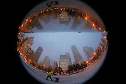 """A worker is reflected in the mirrored sculpture """"Cloud Gate"""" as he sprinkles de-icing salt around the bean-shaped sculpture in Chicago, Illinois, December 16, 2013.  Picture taken with a fish-eye lens.  REUTERS/Jim Young"""