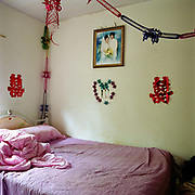 The bedroom of a young married Yao man and Yi woman in Xin Shan (Yao) village, Yunnan province, China. Until recently it was uncommon for a couple from different ethnic minority groups to get married. The People's Republic of China recognises 55 ethnic minority groups in China in addition to the Han majority. The ethnic minorities form 9.44% of mainland China and Taiwan's total population and the greatest number can be found in Yunnan Province, 34% (25 ethnic groups).