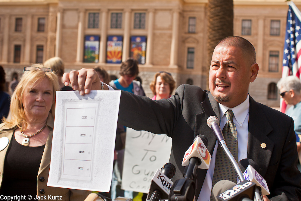 06 FEBRUARY 2012 - PHOENIX, AZ:   Arizona State Senator STEVE GALLARDO, a Democrat, holds up an illustration of a gun lock box while he explains his opposition to a state bill that would allow concealed weapons on college campuses on Monday, Feb. 6. The Arizona State Senate's Judiciary Committee, chaired by Sen Ron Gould (Republican) debated several bills Monday that would loosen the state's gun laws, already among the loosest in the United States. One bill would allow anyone with a concealed carry permit to carry guns on the grounds of public universities. Universities could only ban guns if they provided secured gun lock boxes in each building. Universities, which are opposed to the legislation, say that the lock boxes would cost hundreds of thousands of dollars and that guns would make the campuses less safe. Most of the police departments in Arizona, as well as university student bodies, also oppose the legislation to allow guns on campus.    PHOTO BY JACK KURTZ