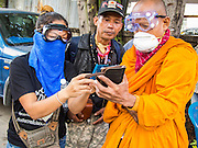 26 DECEMBER 2013 - BANGKOK, THAILAND:   A Buddhist monk uses his smart phone to show pictures of people he said were hurt by riot police while he took shelter with protestors in an apartment block near the Thai Japan Stadium. Thousands of anti-government protestors flooded into the area around the Thai Japan Stadium to try to prevent the drawing of ballot list numbers by the Election Commission, which determines the order in which candidates appear on the ballot of the Feb. 2 election. They were unable to break into the stadium and ballot list draw went as scheduled. The protestors then started throwing rocks and small explosives at police who responded with tear gas and rubber bullets. At least 20 people were hospitalized in the melee and one policeman was reportedly shot by anti-government protestors.    PHOTO BY JACK KURTZ