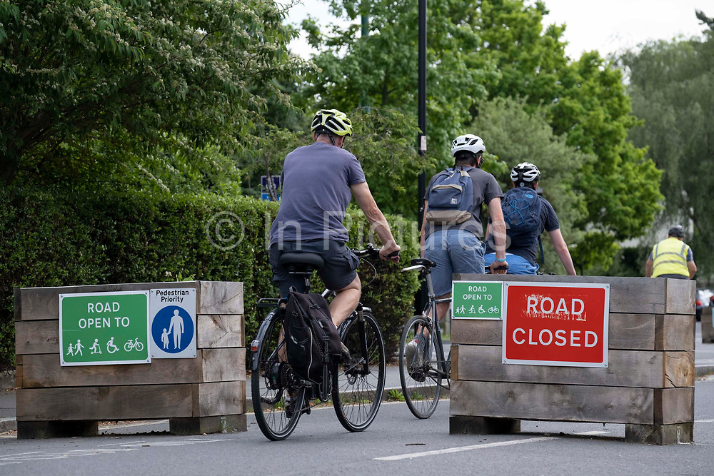 Cyclists pass through the barriers that form an LTN Low Traffic Neighbourhood, an experimental closure by Southwark Council preventing motorists from accessing the junction of Carlton Avenue and Dulwich Village. Restrictions also prevent traffic from passing through at morning and afternoon rush-hour times in the borough of Southwark, on 14th June 2021, in London, England.