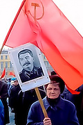 A middle-aged Russian woman supporter, oblivious to the atrocities he committed, carries a photo of Communist strongman, Soviet leader Joseph Stalin during a parade in St. Petersburg, Russia in May 2000. Another Communist Party member behind her carries the Hammer and Sickle Soviet flag.
