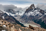 "From Mirador Loma del Pliegue Tumbado, see Cerro Fitz Roy (3405 m or 11,171 ft elevation) rising high above Laguna Torre (634 m or 2080 ft). Clouds hide Cerro Torre. From El Chalten, we hiked to Mirador ""Loma del Pliegue Tumbado"" (""hill of the collapsed fold""), 19 km (11.9 mi) with 1170 meters (3860 ft) cumulative gain in Los Glaciares National Park, in Argentina, Patagonia, South America. El Chalten mountain resort is 220 km north of El Calafate. Chaltén comes from a Tehuelche word meaning ""smoking mountain"", due to clouds that usually form over Monte Fitz Roy. El Chalten mountain resort is in Santa Cruz Province, Argentina, Patagonia, South America."