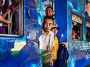25 NOVEMBER 2017 - YANGON, MYANMAR: Passengers standing in the doorway of a Yangon Circular Train arriving in Yangon Central Station. The Yangon Circular Train is a 45.9-kilometre (28.5 mi) 39-station two track loop system connects satellite towns and suburban areas to downtown. The train was built during the British colonial period, the second track was built in 1954. Trains currently run both directions (clockwise and counter-clockwise) around the city. The trains are the least expensive way to get across Yangon and they are very popular with Yangon's working class. About 100,000 people ride the train every day. A a ticket costs 200 Kyat (about .17¢ US) for the entire 28.5 mile loop.    PHOTO BY JACK KURTZ