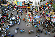 Traffic swirls around a policeman at a roundabout in the busy and noisy main shopping district of Varanasi in Utta Pradesh province, India. (From the book What I Eat: Around the World in 80 Diets.)  Apart from keeping his eye on rickshaws, the policeman is watching for bicycles, pedestrians, cars, and the two cows wandering down the street.