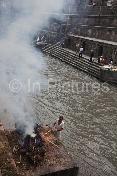 An old man is cremated, his sons lit the fire and the fire is tended to by funeral service men. To burn a body fully takes an estimated 4 hours and hundreds of kilo of wood using butter as fuel. According to Hindu religion and traditions the dead must be burned. Along the Bagmati River next to the Pashupatinath Temple complex are ten alocated spaces for cremation and all day funerals are being held. The bodies are cremated according to custom and the ashes and remains are swept into the holy waters. The Bagmati runs into the Ganges further South and is considered equally holy to Hindus.