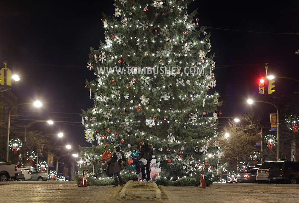 Newburgh, New York - A family stands in front of the tree after the Christmas tree lighting ceremony on Broadway on the night of Dec. 14, 2011.