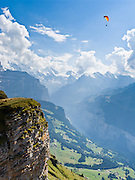"""A paraglider flies over Lauterbrunnen Valley at Männlichen in the Berner Oberland, Switzerland, the Alps, Europe. Lauterbrunnen Breithorn rises to 3780 meters or 12,402 feet elevation in the distance. The world's longest continuous rack and pinion railway (Wengernalpbahn) goes from Grindelwald up to Kleine Scheidegg and down to Wengen and Lauterbrunnen. A gondola (gondelbahn) connects Grindelwald with Männlichen, where a cable car goes down to Wengen (Luftseilbahn Wengen-Männlichen). The Bernese Highlands are the upper part of Bern Canton. UNESCO lists """"Swiss Alps Jungfrau-Aletsch"""" as a World Heritage Area (2001, 2007)."""