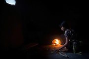 Tabasum Khatun, 14, is lighting up a small fire to cook some rice insider her home in Algunda village, pop. 1000, Giridih District, rural Jharkhand, India.