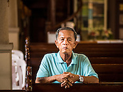 18 SEPTEMBER 2016 - BANGKOK, THAILAND: A man prays in Santa Cruz Church before the church's 100th anniversary mass. Santa Cruz Church was establised in 1769 to serve Portuguese soldiers in the employ of King Taksin, who reestablished the Siamese (Thai) empire after the Burmese sacked the ancient Siamese capital of Ayutthaya. The church was one of the first Catholic churches in Bangkok and is one of the most historic Catholic churches in Thailand. The first sanctuary was a simple wood and thatch structure and burned down in the 1800s. The church is in its third sanctuary and was designed in a Renaissance / Neo-Classical style. It was consecrated in September, 1916. The church, located on the Chao Phraya River, serves as a landmark for central Bangkok.       PHOTO BY JACK KURTZ