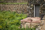 A stone dwelling next to a terraced vineyard on Pantelleria Island, Sicily.