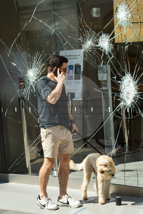 Charleston, United States. 31 May, 2020. A pedestrian stops to view the shattered glass store front of the Apple Store on the King Street shopping district after a protest over the death of George Floyd, turned violent and destructive May 31, 2020 in Charleston, South Carolina. Floyd was choked to death by police in Minneapolis resulting in protests sweeping across the nation.  Credit: Richard Ellis/Alamy Live News