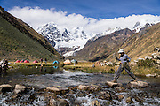 A hiker steps on stones across Rio Jahuacocha to Incahuain campground below Mount Jirishanca (Icy Beak of the Hummingbird, 6126 m or 20,098 feet). Day 8 of 9 days trekking around the Cordillera Huayhuash in the Andes Mountains, one day's walk from LLamac, Peru, South America.