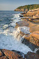 Surf breaking on colorful pink granite of Otter Point, Acadia National park Maine USA