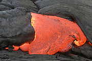 Molten lava flows from an opening at the end of a lava tube from the Pu'u O'o Kila vent in Volcanoes National Park on Hawaii.