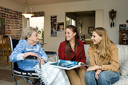 Stanford hospice care students Jessy Klima (blonde) and Victoria Whittaker show pictures of Hawaii to Helen Fineberg's mother.