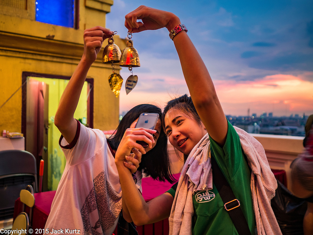 """20 NOVEMBER 2015 - BANGKOK, THAILAND:  Girls take """"selfies"""" with an iPhone of the prayer bells they donated at the chedi on top of Wat Saket during the annual temple fair. Wat Saket is on a man-made hill in the historic section of Bangkok. The temple has golden spire that is 260 feet high which was the highest point in Bangkok for more than 100 years. The temple construction began in the 1800s in the reign of King Rama III and was completed in the reign of King Rama IV. The annual temple fair is held on the 12th lunar month, for nine days around the November full moon. During the fair a red cloth (reminiscent of a monk's robe) is placed around the Golden Mount while the temple grounds hosts Thai traditional theatre, food stalls and traditional shows.    PHOTO BY JACK KURTZ"""