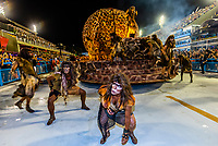 """The Carnaval parade of Estacio de Sa samba school in the Sambadrome, Rio de Janeiro, Brazil.           <br /> <br /> The theme  of their parade is """"Stones"""" which includes a 2001:A Space Odyssey type scene with cavemen watching a rock open into a spacecraft with astronauts coming out."""