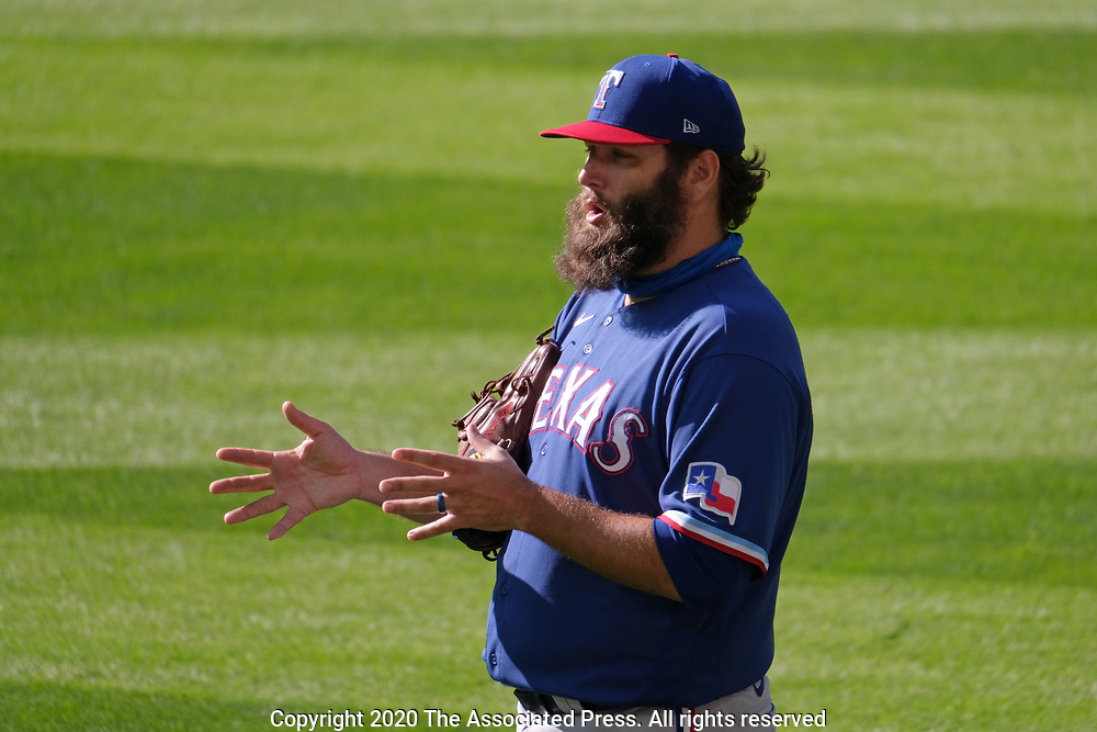 Texas Rangers pitcher Lance Lynn stands in the outfield and talks with other players during batting practice before a baseball game against the Seattle Mariners, Saturday, Aug. 22, 2020, in Seattle. (AP Photo/John Froschauer)