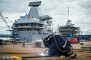 The finishing touches are being put onto the Aircraft Carrier HMS Queen Elizabeth at the naval dockyard in Rosyth in the run up to the ship's naming ceremony.<br /> <br /> A welder is finishing work on the ski ramp section of the flight deck. <br /> <br /> © John Linton<br /> All rights reserved