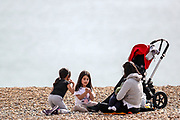 People enjoy the Sunny weekend as they sit and lay along the Brighton Beach on Sunday, April 11, 2021. <br /> On Monday, April 12, England enters the next stage of government's roadmap out of lockdown, when the non-essential shops, outdoor hospitality, and personal services including hairdressing can open again. (Photo/ Vudi Xhymshiti)