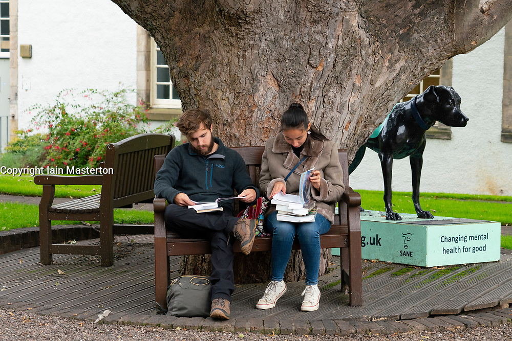 St Andrews, Scotland, UK. 7 September, 2020. Freshers Week starts at the University of St Andrews in Fife. Overseas and domestic students are arriving in the town this week. Many students are accompanied by their parents and were exploring the ancient university campus and the major attractions in the town. Pictured; Students browsing books in courtyard next to university library.  Iain Masterton/Alamy Live News