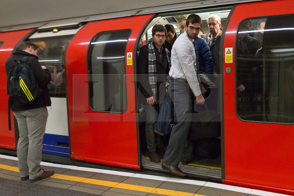 """© Licensed to London News Pictures. 18/01/2016. Commuters on the busy Waterloo and City tube line this morning. London, UK. Today, known as """"Blue Monday"""" is meant to be the most depressing day of the year. Photo credit : Vickie Flores/LNP"""