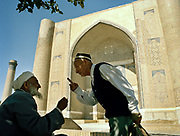 Uzbeks speaking theology in front of Bibi-Khanym Mosque in the fabled city of Samarkand, on the ancient Silk Road. Uzbekistan.