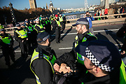 Thousands of Extinction Rebellion activists took over 5 bridges in Central London and blocked them for the day, November 17 2018, Central London, United Kingdom. Lambeth Bridge; an elderly quaker man is arrested and taken away by police. Around 11am people on all bridges sat down in the road and blocked traffic from coming through and stayed till late afternoon. The actvists believe that the government is not doing enough to avoid catastrophic climate change and they demand the government take radical action to save future generations and the planet. Many are willing to be arrested peacefully protesting and up to 80 were arrested on the day. Extinction Rebellion is a grass root climate change group started in 2018 and has gained a huge following of people commited to peaceful protests and who ready to be arrested. Their major concern is that the world is facing catastropohic climate change and they want the British government to act now to save future generations.