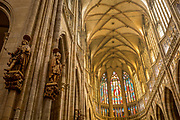 Nave Of St Vitas' Cathedral in Prague Castle, on 18th March, 2018, in Prague, the Czech Republic. The Metropolitan Cathedral of Saints Vitus, Wenceslaus and Adalbert is a Roman Catholic metropolitan cathedral in Prague, the seat of the Archbishop of Prague. Until 1997, the cathedral was dedicated only to Saint Vitus, and is still commonly named only as St. Vitus Cathedral. This cathedral is a prominent example of Gothic architecture and is the largest and most important church in the country. It is located within Hradcany-Prazsky Hrad (Prague Castle) in the Czech capital.