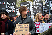 Whitehall November 28th Protest organised by Stop the War against the proposed bombing of Syria. A young man holds a home-made sign saying 'Bombing doesn't kill an ideology, it feeds it', and a young woman next to him has a home-made sign saying 'War won't work'.
