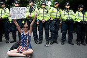 Balcombe, West Sussex. Site of Cuadrilla drilling. Demonstration against fracking 18.08.2013. A protester sits on the ground in front of a line of police and holds up a sign saying 'No fracking here or anywhere. We must utilise wind, sun and sea'.