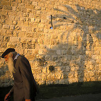 Israel, Jerusalem, Man walks past shadows of palm trees along city's ancient walls