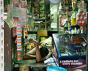 A shop owner takes a nap in his store.
