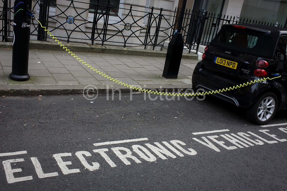 A parked Smart car recharges electric power at an EDF charging point in central London. Its yellow coiled cable stretching from charging point to car. Source London is now the capital's largest charging network. It has significantly boosted existing numbers of charge points operated by a range of different localised schemes. By 2013, Source London will total at least 1,300 charge points, more than the number of petrol stations currently in London, ensuring the infrastructure is in place for significantly more people and businesses to buy an electric vehicle. The creation of an electric vehicle network is in line with the Mayor's pledge to promote quality of life by reducing pollution and CO2 emissions.