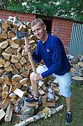 Polish teen wood chopper holding ax beside large pile of split wood. Zawady Central Poland
