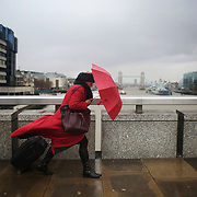 A women in red crossing Londong Bridge in bad weather. London Bridge connects the City of London and London Bridge train station and many city workers uses the the bridge. This was a windy and rainy morning and the woman was struggling to keep her umbrelly from blowing away.