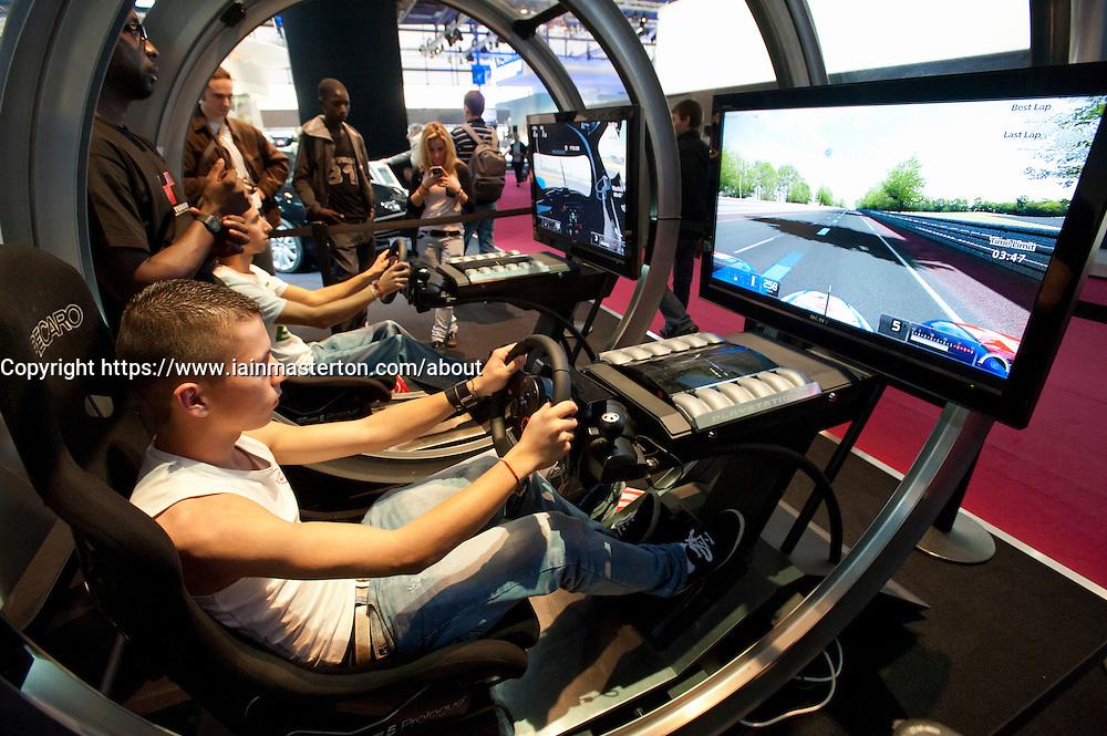 Visitors using Playstation driving simulator at Paris Motor Show 2010