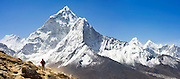 Liana Welty is dwarfed by the massive North Face of Ama Dablam (6848m), as seen from above Dingboche along the trail to Everest, Khumbu region, Sagarmatha National Park, Himalaya Mountains, Nepal.